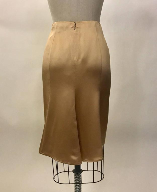 """Gianni Versace Couture 1990s light gold silk skirt with a slight fishtail detail at back hem. Back zip and hook and eye.  100% silk. Fully lined in 100% rayon.  Made in Italy.  Size IT 40, approximate US 4. Waist 27"""". Hip 38"""". Length (top"""