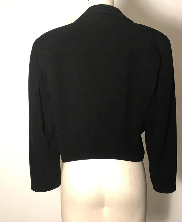 Vintage 1980s black wool biker jacket from Stephen Sprouse's Sprouse line. Asymmetrical styling with three zipper pockets at front, one mini flap pocket, zip closure, and zipper detailing at cuffs.   100% wool. Fully lined in a satiny fabric.  Size