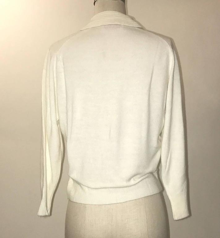 Schiaparelli 1960s super soft white cardigan sweater with rib knit collar detail, beaded floral design at side, and rhinestone buttons.  Signed 'styled by Schiaparelli Paris at label.'  No content label, feels like an extra soft blend of wool/angora
