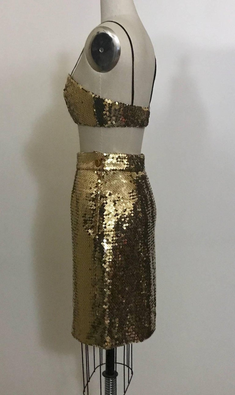 Early 1990s gold sequin cropped bustier and matching skirt by Franco Moschino. Bustier has thin black straps that can be worn or tucked in and fastens with hook and eyes at back, lined in black. Skirt fastens with side zip and snap, decorative