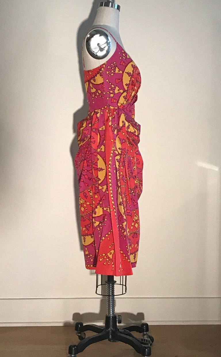 Christian Dior pink and yellow tassel pendant print dress. Draped detail creates volume at waist and a bow like flourish at side. Side zip and hook and eye.  51% cotton, 49% silk. Fully lined in 100% silk.  Made in France.  Labelled size FR 38, US 6