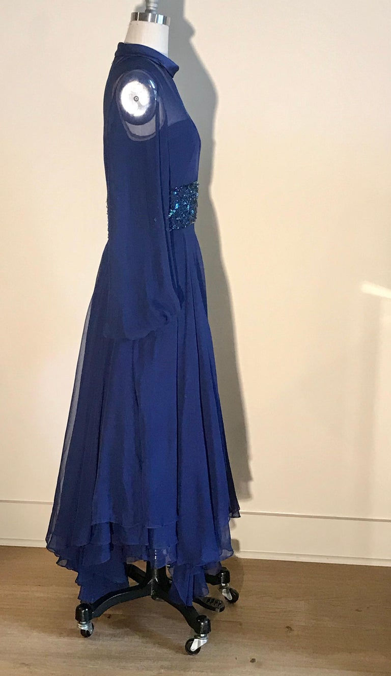 William Travilla vintage cobalt blue dress (estimated 1970s) featuring sheer detailing and beaded embellishment at waist. Amazing layered skirt has tons of movement. Wide sheer sleeves are banded at wrist to create volume. Nude lining at top. Back