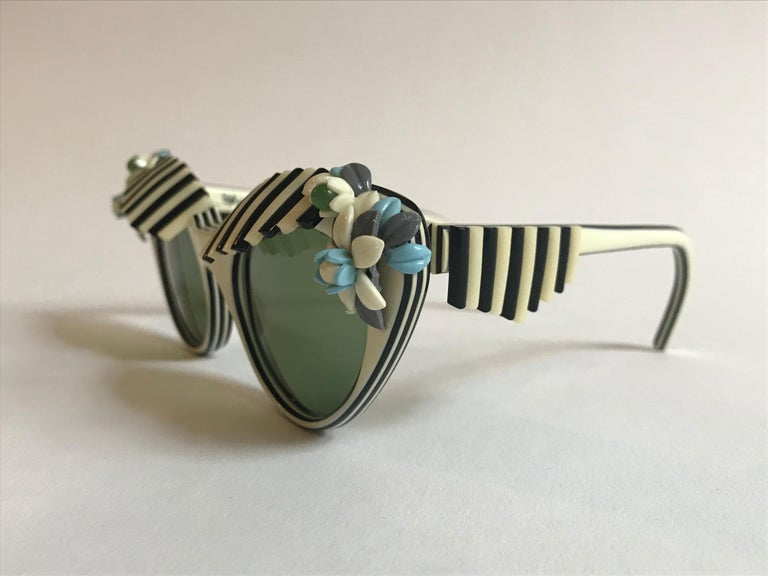 Elsa Schiaparelli 1950s vintage sunglasses in a creamy white with black accents. Black and white pieces form cabana style shades over the top of the lense and at sides. cream, baby blue, and olive green floral accents at corners of cat eyes. A