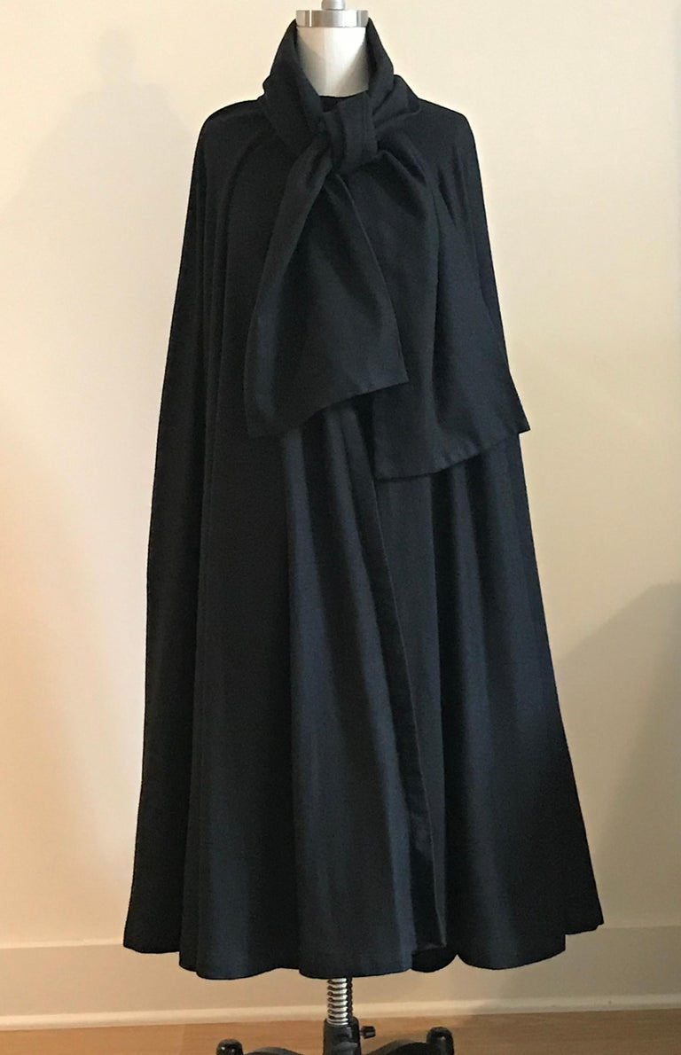 Geoffrey Beene vintage 1970s black cape with a faint herring bone weave. Closes at neck with a snap and hook. Wide scarf detail at collar Can be tied and let hang, or tucked in around neck to create a more sculptural look. Hits between knee and