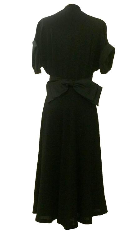 Late 1940's dress from American designer Nettie Rosenstein in black crepe. Pleating at bust, black heavy-faille sash with bow at back, as well as black faille trim at sleeve cuffs. Falls at mid-calf. Side zip. Lined at skirt. 
