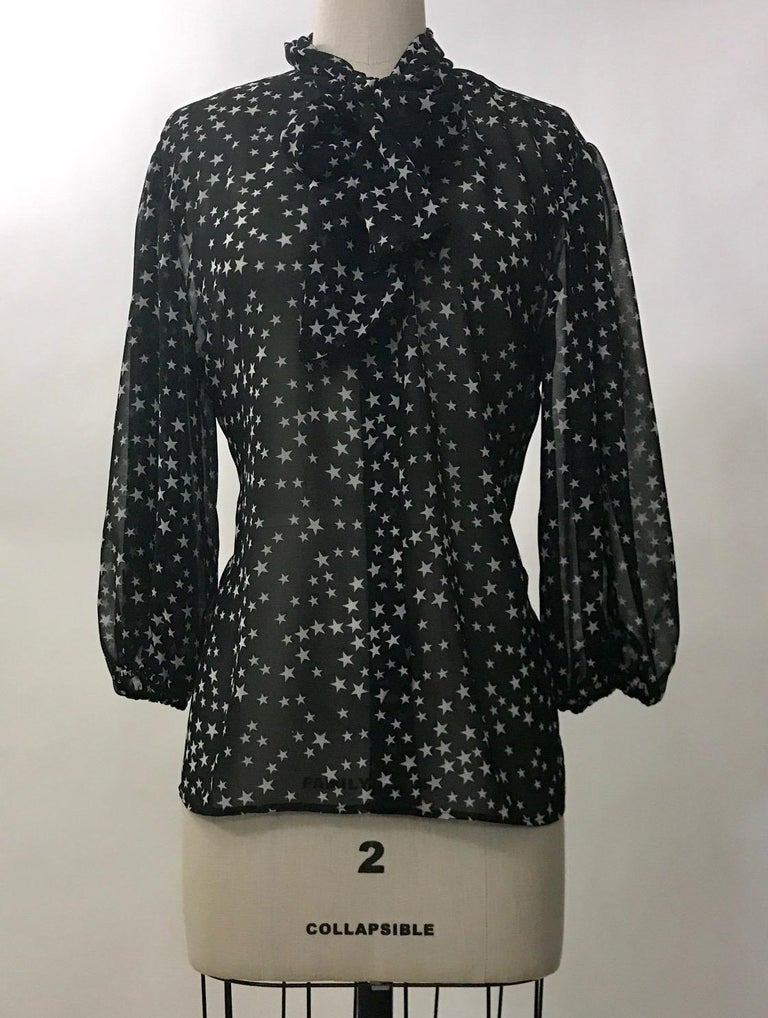 Dolce & Gabbana semi-sheer black and white star print blouse from the Fall 2011 collection. Fabric at neck can be tied as a pussycat bow or left to hang for a scarf like look. Elastic at cuffs creates a slightly voluminous sleeve. Button