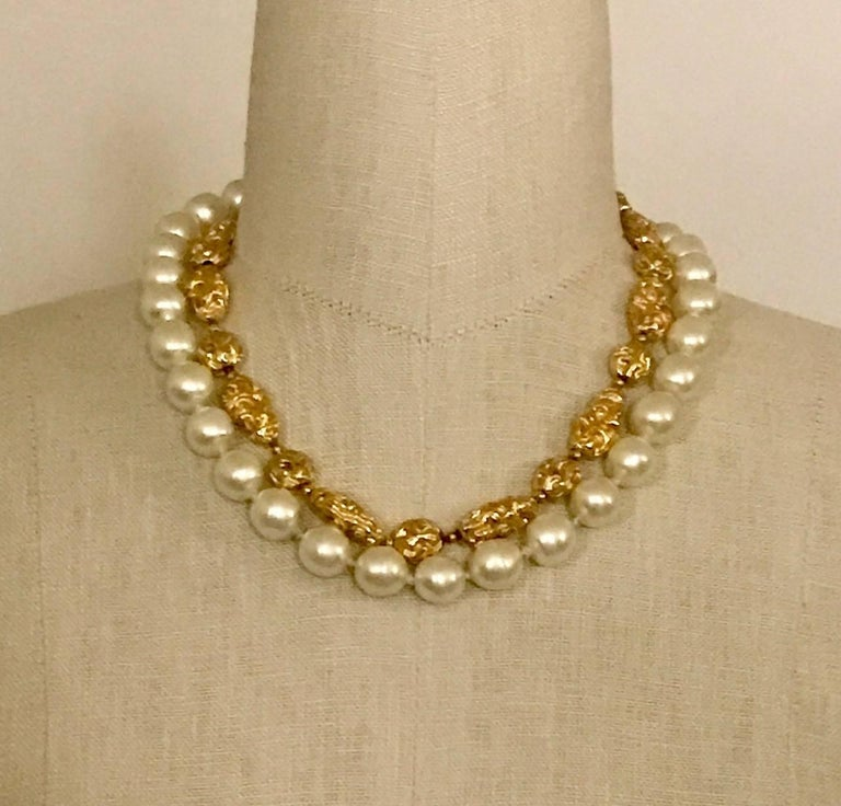 Very rare Chanel vintage 1970's necklace featuring a strand of faux gold nuggets and one of faux pearls. Spring ring closure.  Measures approximately 16