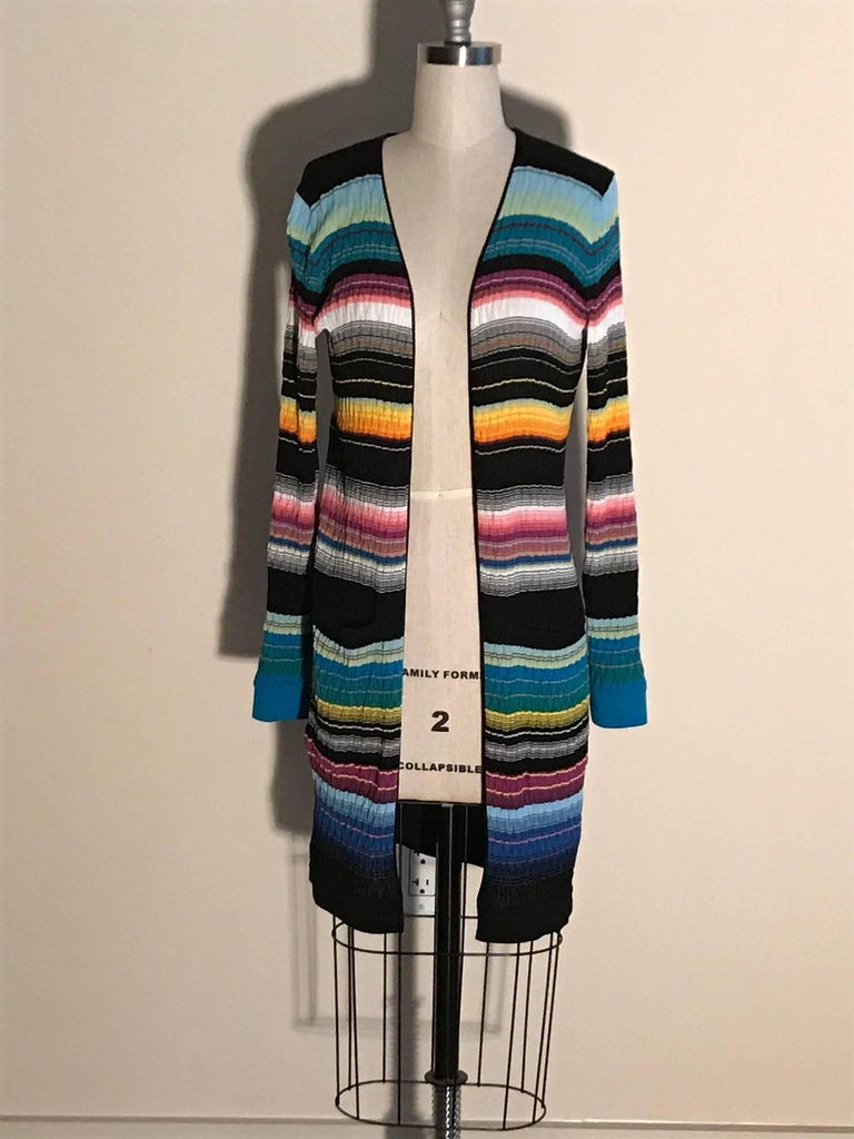 Missoni stripe knit long sleeve sweater with varying shades of teal, fuchsia, goldenrod, black, and cream.  Textured with a chevron pattern ribbing. Pockets at both sides of front hip. Open front, no fasteners.   67% cotton, 31% rayon, 2%