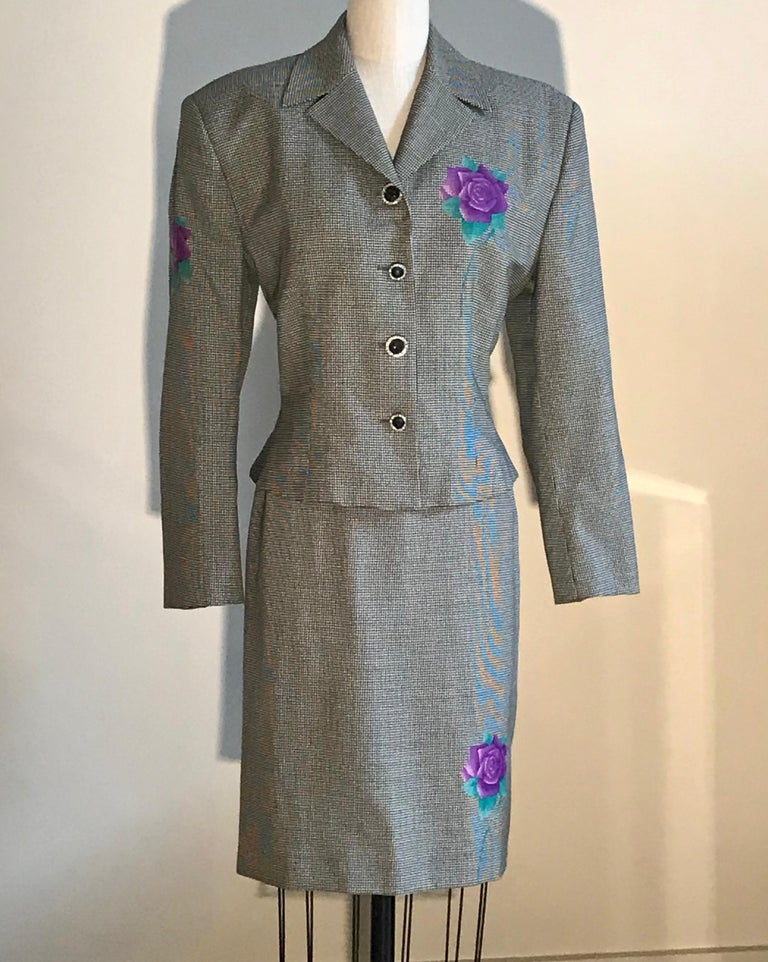 Gianni Versace vintage wool skirt suit in black and white houndstooth or dogtooth check. Purple and green roses printed at jacket bust, one sleeve, and back, as well as on front and back skirt. Jacket features purple Versace logo buttons with