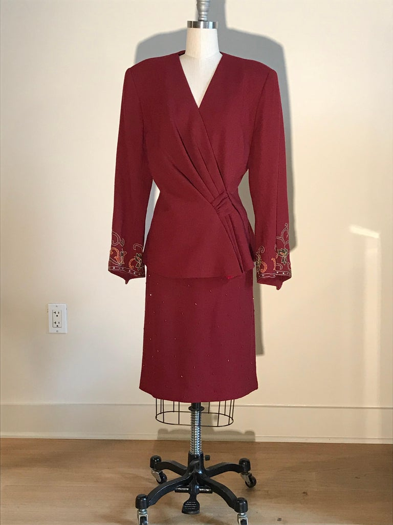 Pierre Balmain vintage 1980s cranberry red wool skirt suit featuring beading at skirt at embroidery and rhinestone embellishment at diagonally hemmed sleeves. Skirt has back zip, jacket fastens with a snap and two hook and thread closures.  100%