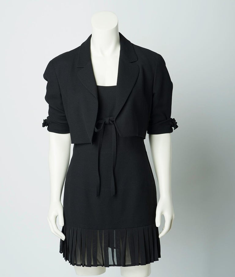 Claude Montana vintage 1980s black mini dress and cropped jacket set.  Black sleeveless dress features sheer pleated trim and tie detail at empire waist. Open front jacket features tie detail at sleeves.  40% viscose, 40% wool, 20% silk. Trimmed in