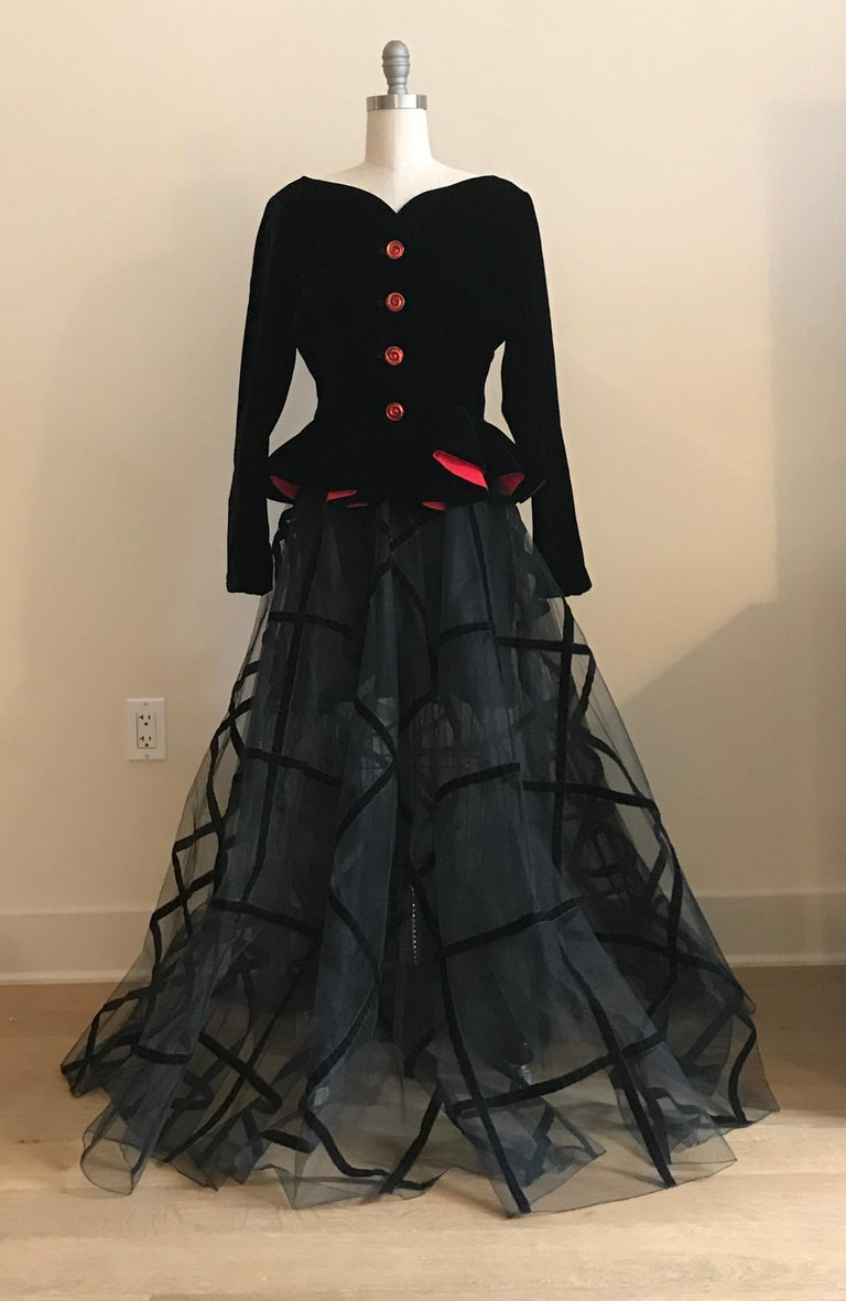 Yves Saint Laurent Rive Gauche 1990s skirt suit featuring a black double layered tulle ball gown style skirt with black velvet trim and a black velvet jacket with red lining and gold and red novelty buttons. Skirt is semi sheer with an attached