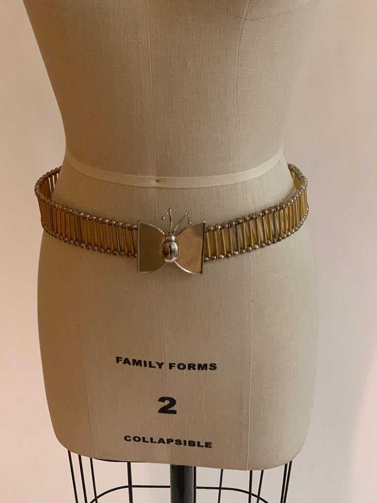 William De Lillo metal butterfly belt in silver and gold tones. Long silver and gold tone metal beads connect  silver ball pieces at edges. Fastens with two hooks at back of butterfly.  Stamped 'de Lillo' at butterfly back.  Adjustable up to 30