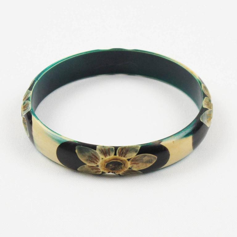 Lovely vintage Art Deco celluloid bracelet bangle. Featuring floral design, four motif all around the bracelet deeply carved, painted and stained. Assorted colors of teal, off-white, yellow and black. France, circa 1925s. Excellent vintage