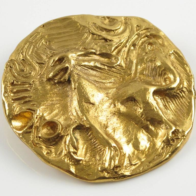 YVES SAINT LAURENT YSL Paris signed Pin Brooch. Rare vintage elegant gilt metal massive round shape worked like an antique coin, metal all textured with hand-made feel featuring a dimensional mythical lion. This pin brooch can also be used as a