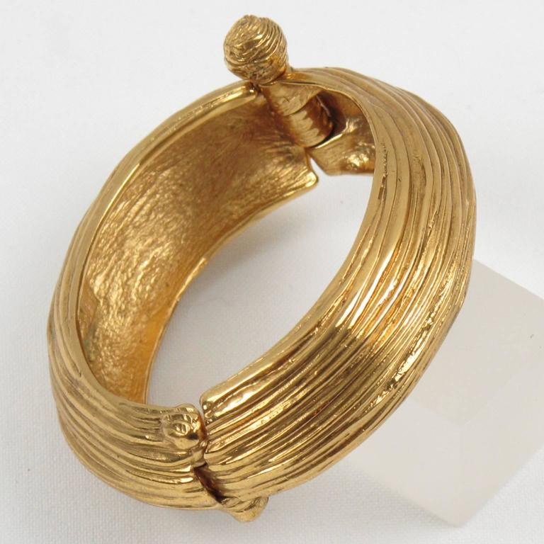 "Elegant Yves Saint Laurent YSL Paris signed clamper bracelet. Featuring an ovoid oversized shape with gilt metal all carved and textured. Bracelet is hinged and opens with a push/pull stick lock closure. Signed in the inside with ""YSL - Made in"