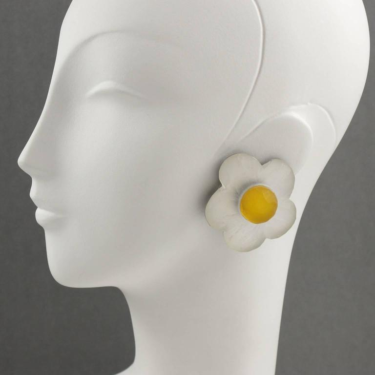 Gorgeous oversized frosted lucite clip on earrings designed by Harriet Bauknight for Kaso. Impressive large dimensional shape all carved and textured featuring a daisy flower in frosted white and yellow colors and clip back. Signed at the back with