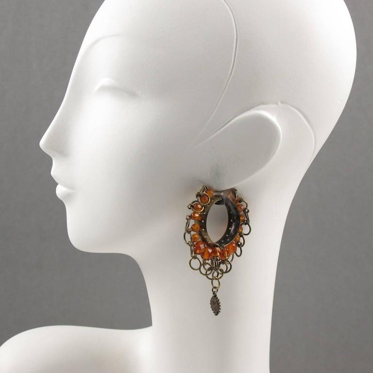 "Rare vintage Jean Paul Gaultier Paris signed clip on earrings with Gothic inspiration. Large hoop shape in gilded metal with aged patina ornate with metal rings and orange glass faceted beads charms. Dangling ""JPG"" logo signature. Gaultier's designs"