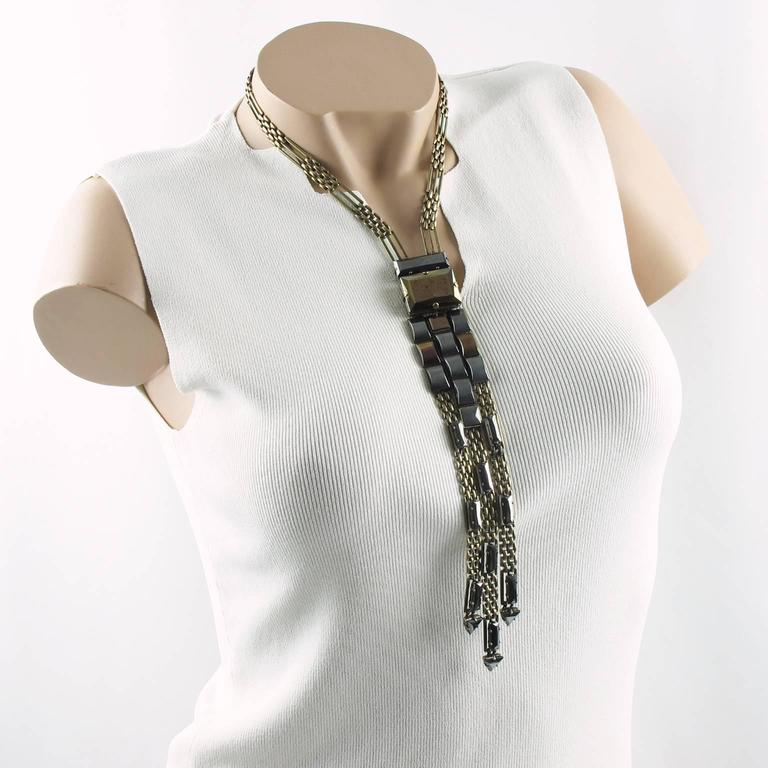 Stunning 1990s Jean Paul Gaultier Paris signed tie necklace. Dramatic extra long dangling shape with gilt metal in antique bronze patina, compliment with metallic rhinestone cabochons in bronze and gun metal colors. Locking box clasp with security