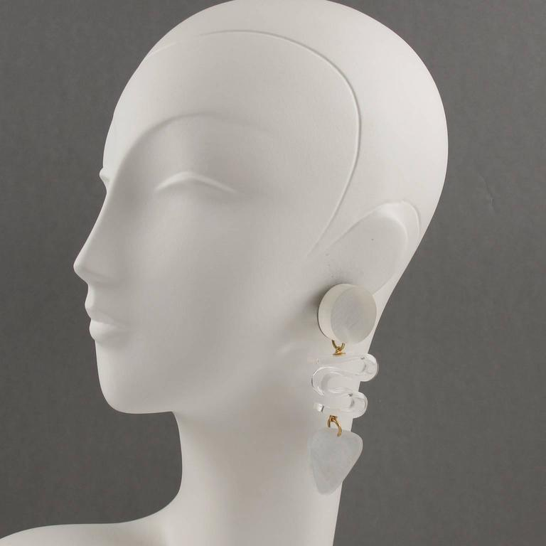 Stunning oversized Lucite clip on earrings designed by Harriet Bauknight for Kaso. Huge chandelier dangling shape featuring dimensional geometric design in frosted white color compliment with twisted clear Lucite element. Signed at the back with