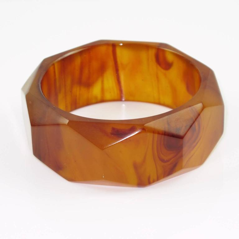 Vintage root-beer marble Bakelite carved bracelet bangle. Sliced shape with deep faceted carving all around and thick wall. Intense root-beer marble tone with amber and brown cloudy swirling, lots of translucency. Excellent vintage