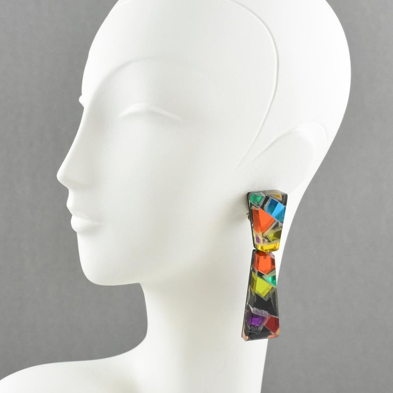 Colorful oversized Lucite chandelier clip on earrings designed by Harriet Bauknight for Kaso. Large dangling shape with geometric design featuring dimensional multilayer black lucite with colorful harlequin mirrored effect inclusions. Assorted