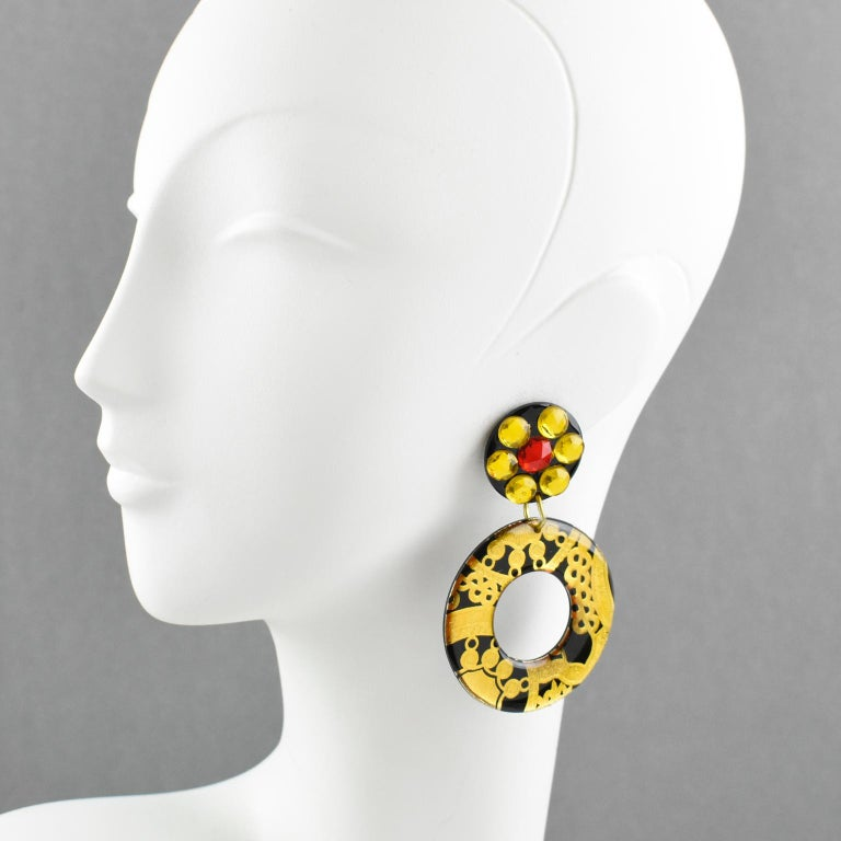 Incredible Italian designer studio Lucite or resin dangling clip on earrings. Oversized hoop shape with baroque design in black and gold colors. Earrings are also ornate with saffron and red glass rhinestones. Total eye catching Pop Art statement