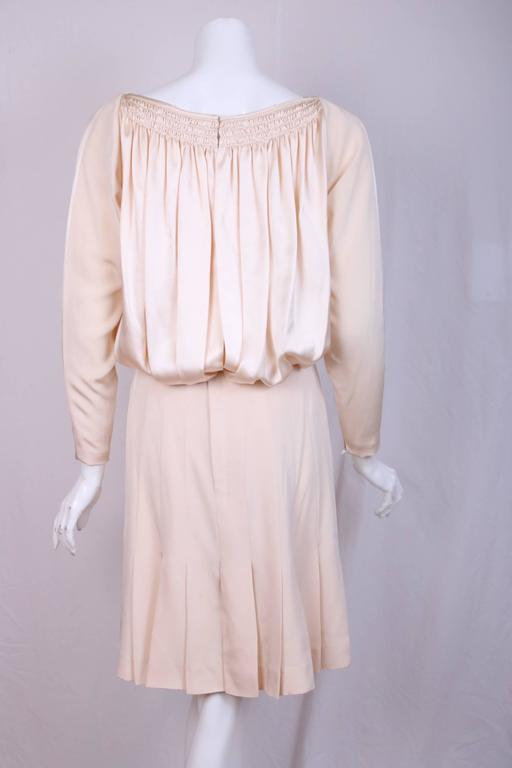 Vintage Galanos silk charmeuse & silk twill cocktail dress. The top is done in silk charmeuse with 3 rows of delicate smocking that create soft gathers that cascade to create a blouson effect. The skirt is pleated silk twill that falls just above