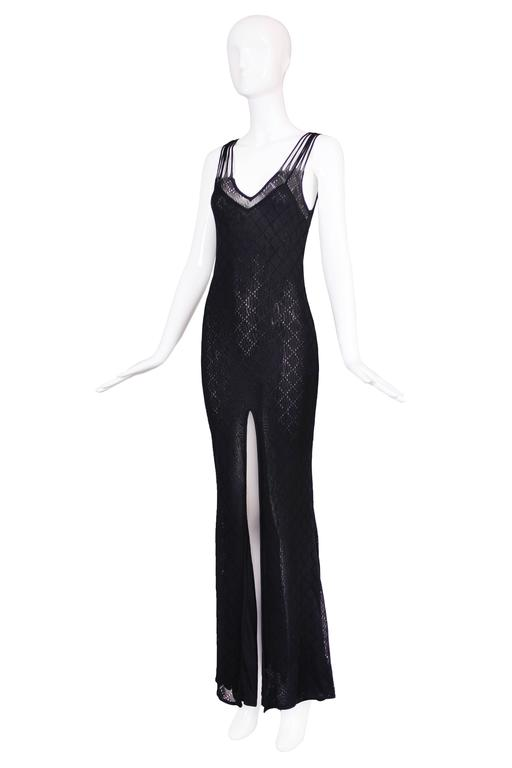 Christian Dior black sleeveless evening gown with dramatic frontal slit, diamond pattern and illusion back. In excellent condition. Size tag US 8, fabric is 100% viscose.