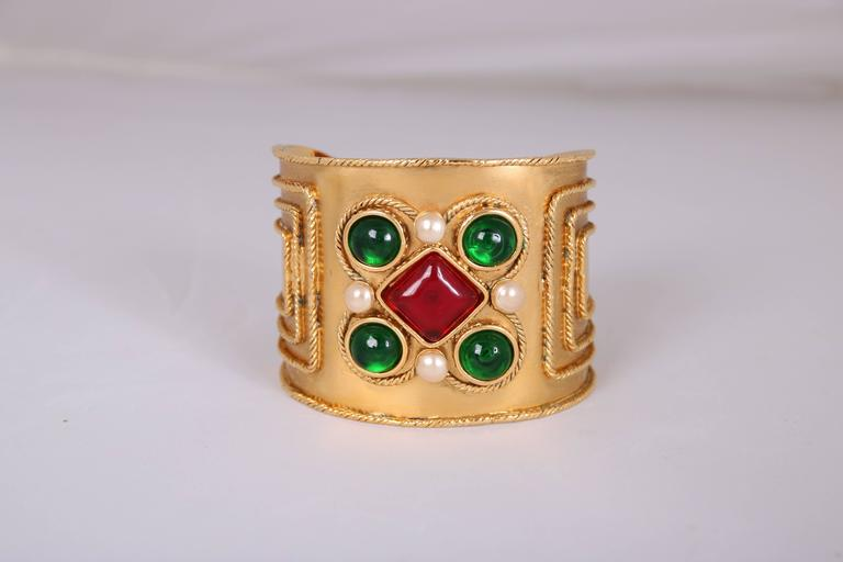 2005 Chanel cuff featuring bezel set pearl beads and green and red gripoix stones. Stamped on Chanel cartouche at interior. In excellent condition.