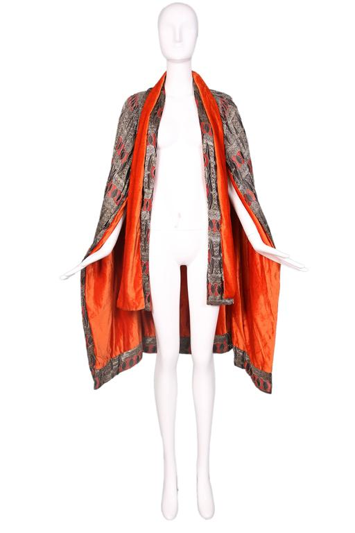 1920's geometric print cape made from gold metallic thread, black and red silk and an interior of orange silk velvet. Cape features two sets of neck ties that drape down the front. Cape isn't labeled but style, design and print reminiscent of Paul