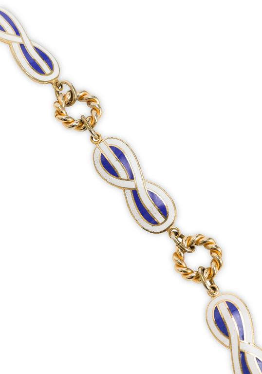 """1970's Gucci link belt/necklace fashioned from an alternating pattern of textured gold tone rings and figure eight shapes in blue and white enamel. Features a toggle clasp closure. Stamped """"Gucci"""" on toggle clasp bar. In excellent condition with"""