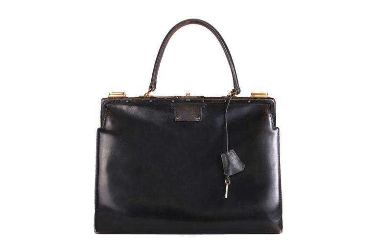 Vintage Hermes black leather handbag with lock & key. Features gold hardware and black leather interior. In good vintage condition with minor scratches and scuffs at the interior and exterior. There is some peeling of the leather covering the metal