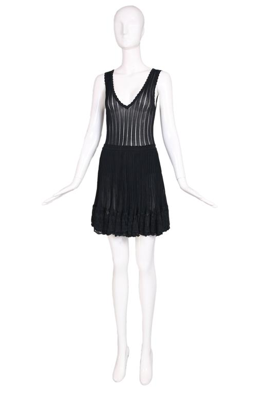Azzedine Alaia black ballerina sheer stretch mini dress w/V-neck and scalloped, lace-trimmed hem. Back skirt has a layered mini waterfall hem. In excellent condition with a few loose threads along the bottom and some minor, barely noticeable pulls