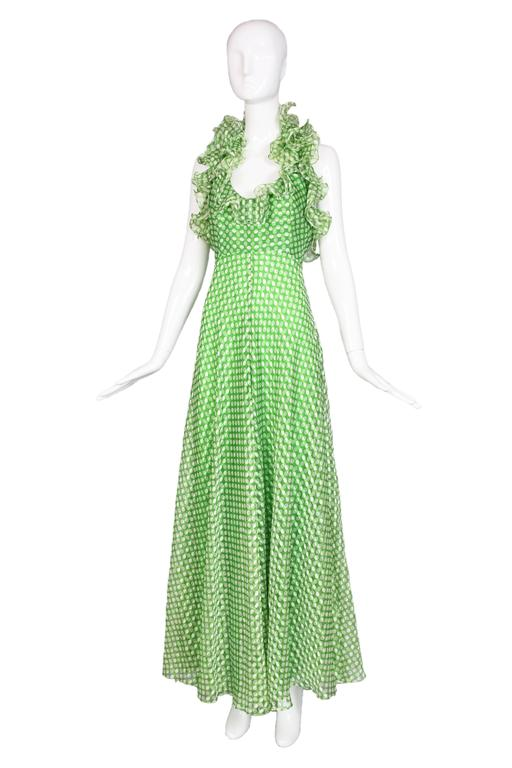 """1970's Geoffrey Beene green & white polka dot halter dress featuring ruffled trim. Fully lined. In excellent condition. No size tag, please consult measurements. MEASUREMENTS: Bust - 33"""" Waist - 26"""" Hip - 46"""" Length - 56"""""""