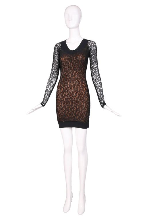 """Alaia black lace body hugging mini dress with bronze-colored underlay and sheer lace sleeves. In excellent condition. Size S.  MEASUREMENTS: Bust - 30"""" Waist - 26"""" Hip - 36"""" Length - 31"""" Shoulder - 14"""" Sleeve -"""