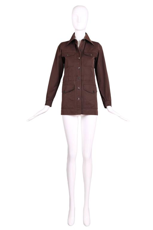 1970's Yves Saint Laurent brown cotton safari jacket with four frontal pockets and elastic waistline. No size tag, please consult measurements. In excellent condition - please note, the elastic waistline may need to be replaced. MEASUREMENTS: Bust -