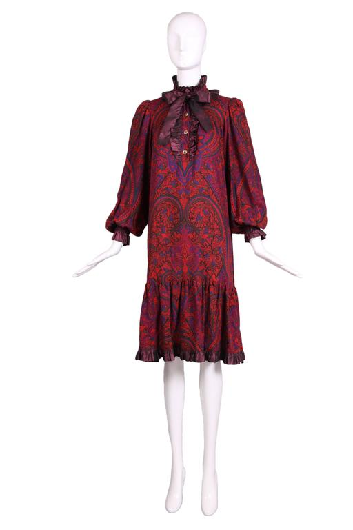 1970's Yves Saint Laurent light-weight wool paisley print smock dress in shades of purple, green, blue and orange-red with purple taffeta ruffled trim. Features metal paisley design buttons and hidden pockets at either side seam. In excellent