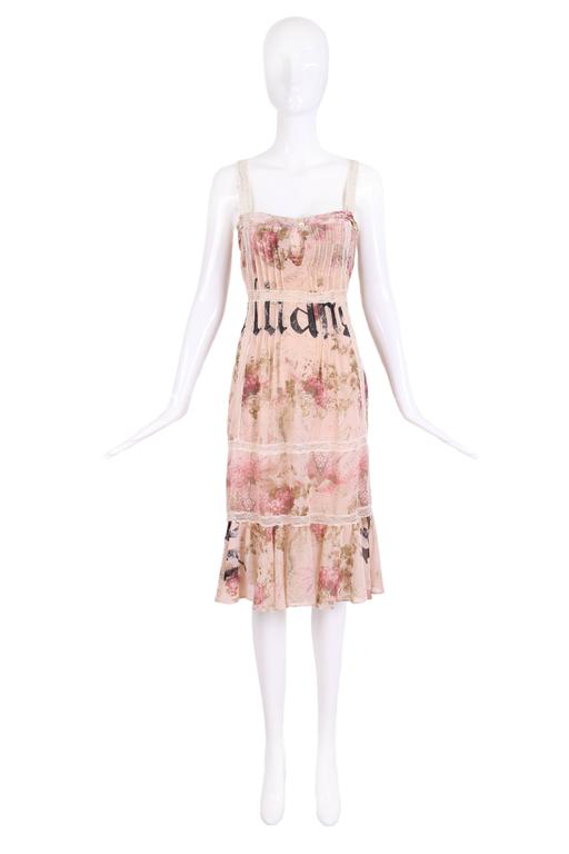 John Galliano rayon floral and signature dress with built in bra. Dress has cream lace insets, pintuck detailing and a soft ruffle flounce hem. In excellent condition. Size 40.