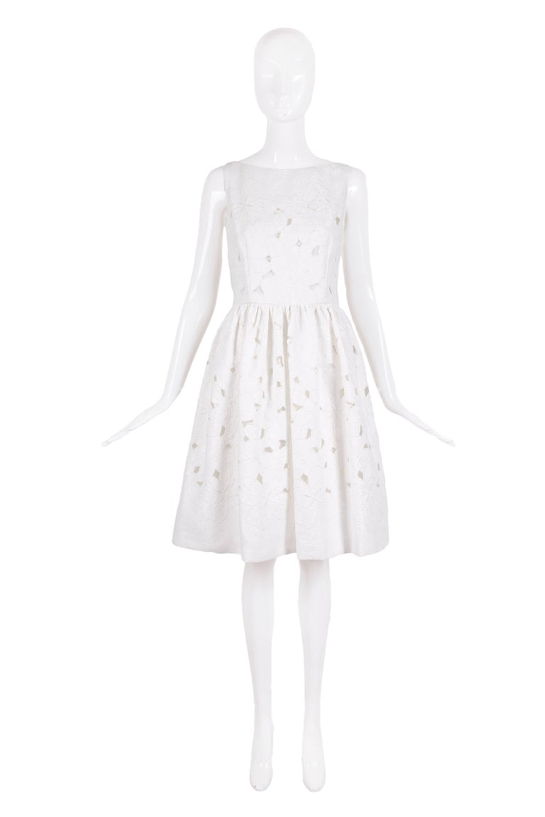 "2013 Dolce & Gabbana white cotton sleeveless day dress with floral cutout pattern throughout. Fully lined, size tag 44 - dress has never been worn and still has original tags attached. In excellent condition. MEASUREMENTS: Bust - 38"" Waist -"