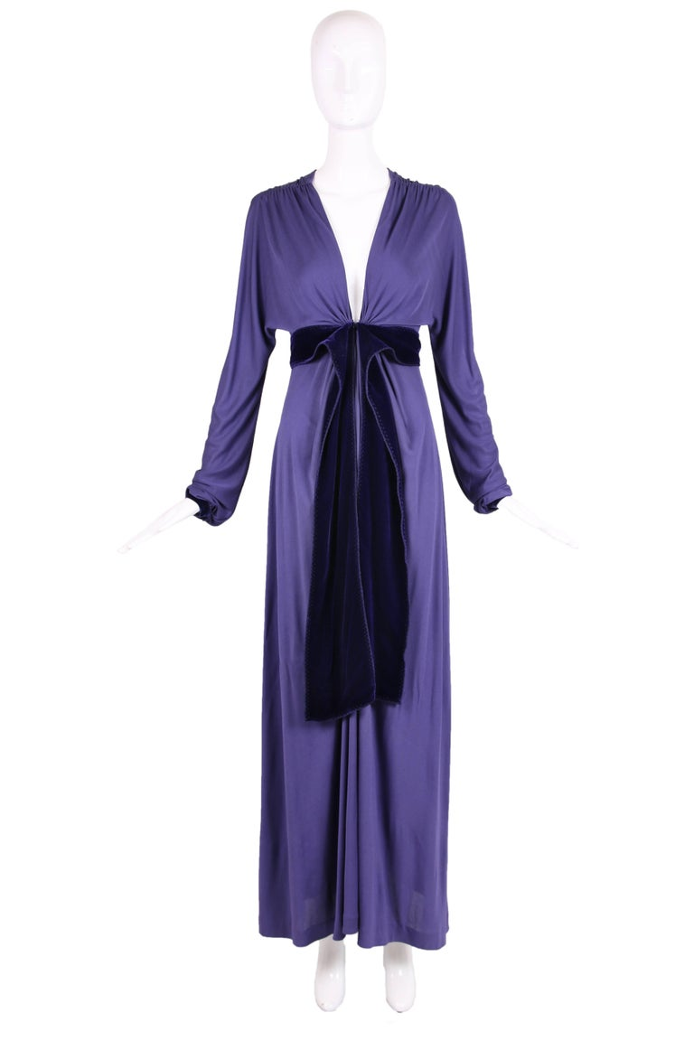 Yves Saint Laurent by Tom Ford purple maxi dress with plunging neckline, empire waist, and extra long sleeves. Ruching at the shoulders and waist with a thick deep purple velvet band to be worn open or tied at front waist. Deep purple velvet trim