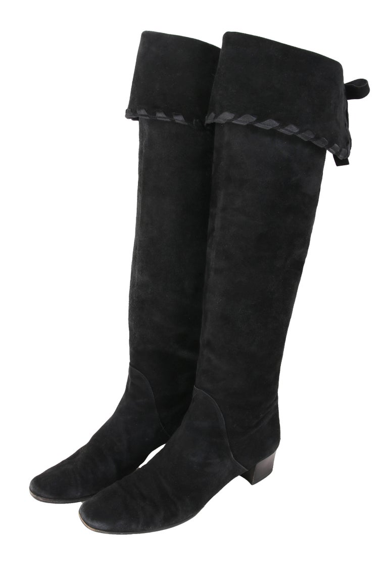 Vintage Yves Saint Laurent YSL black suede boots that can be worn as either knee-high or thigh-high. Top of boot is finished with satin ribbon and decorative leather ties at back. The boots are stamped Yves Saint Laurent at interior at the foot pad