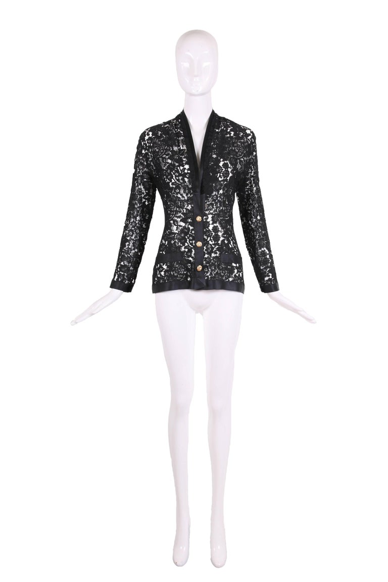 Vintage Chanel black lace jacket with black silk trim & goldtone Camellia buttons w/a pearl at the center. In excellent condition - size tag 36.