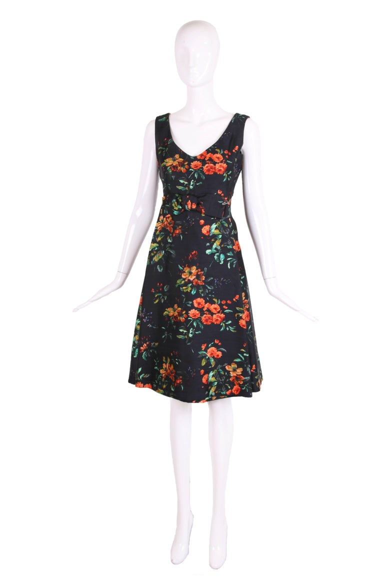 1960's Christian Dior navy blue silk shantung v-neck sleeveless dress in vibrant orange and green floral pattern. The dress features a tubular front panel, cropped back panel overlay, and frontal bow at the waist. In excellent condition. No size