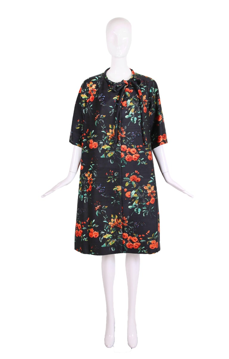 1960's Christian Dior navy blue silk shantung swing coat featuring vibrant orange and green floral print. The coat has 3/4 sleeves, two hidden snap closures at the top with neck ties. Fully lined in orange silk. In excellent condition. No size tag,