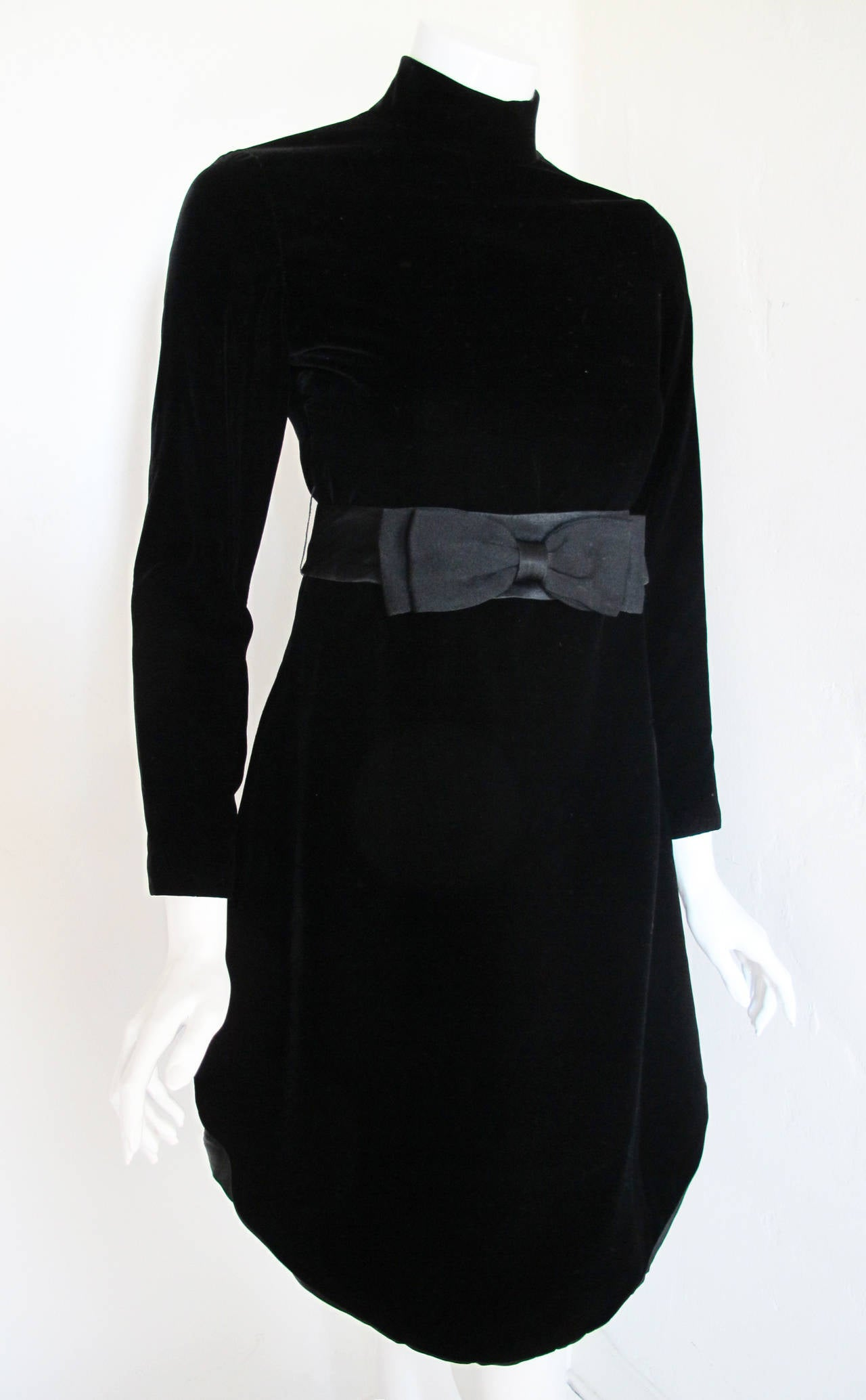 "A black velvet 1970s Pierre Cardin cocktail dress with set-in long sleeves, stand collar and slits at the side. This dress appears to be a variation on a Cardin classic, the ""chasuble dress"" with its Cardin-esque tabard over-layer and rounded"