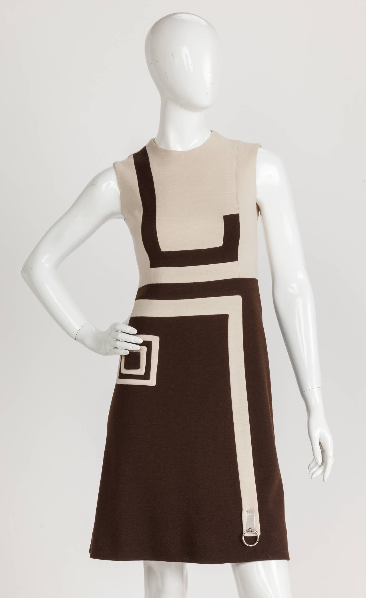 A Pierre Cardin sleeveless wool jersey dress in creme and brown with graphic print design. I'm such a fan of this hip and sophisticated mod day dress with its flared skirt and modern decorative elements: a square inside a square appliquéd at the