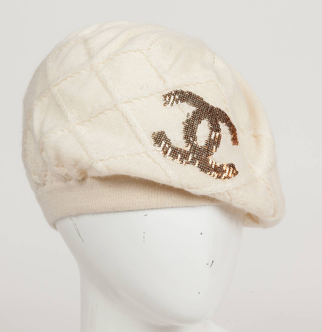 A Chanel 100% cashmere creme-colored beret/hat with a repeated pattern of raised, knitted lattice design and the CC logo embroidered with mini-gold and bronze sequins. The cashmere is incredibly soft, stretchy and the knit is quite small. The hat