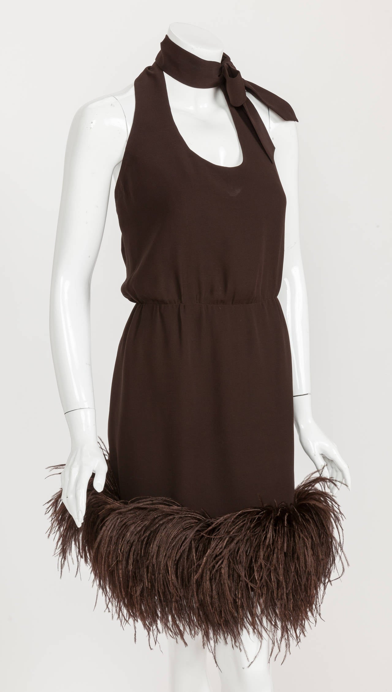 A mid-1960s Pierre Cardin haute couture brown chiffon halter dress with neck bow and Ostrich feather trim. While Pierre Cardin is credited with co-creating the Space Age in fashion, he was first and foremost a master couturier. And this mid-1960's