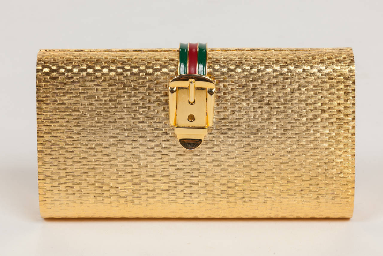 "A 1970s Gucci limited edition minaudière, clutch made of gold-colored metal in a basket weave pattern and featuring a clasp comprised of the classic Gucci ""buckle"" closure with red and green racer stripe enameling. Hinges open at the bottom and is"